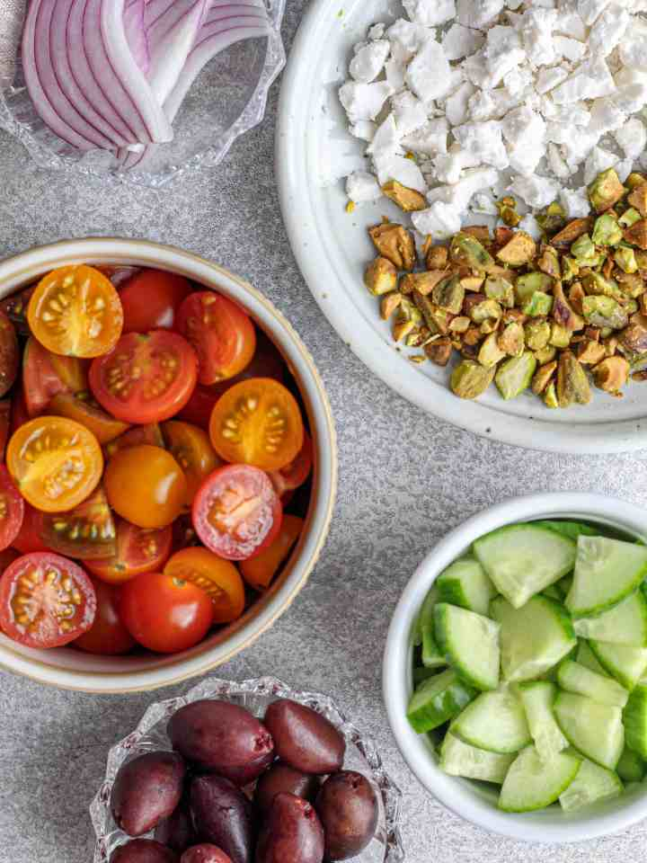 Preparation for salad with vegan feta, pistachios, red onion, olives, cucumbers and tomatoes