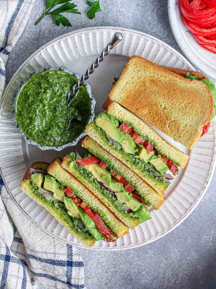 Avocado and Herb Pesto Sandwich with red onion, tomato, and toasted brioche.