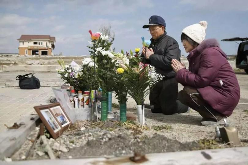 Tsutoshi Yoshida e sua esposa, Seiko oferecem orações em Namie, na província de Fukushima, onde funcionava uma estação de correios e na qual perderam a filha Miki após no tsunami de 2011 (Foto: Kyodo)