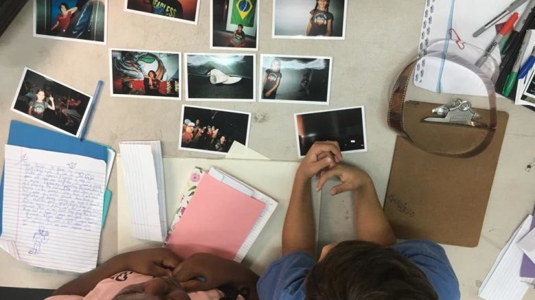 two children looking down at a table with printed photos