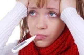 chica con termómetro en la boca y fiebre
