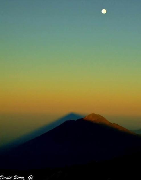 Amanecer en el volcán Tajumulco - volcán más alto de C.A. 4,220 m - la sombra sobre el volcán Tacaná y la luna adornando - foto por David Perez