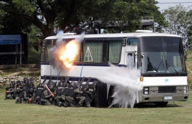 PNP members of the SAF detonate an improvised bomb on a main door of a mock tourist bus during a crisis response group demonstration inside police headquarters in Bicutan