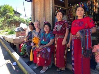 group of Guatemalan women from CEMIK sit with Joan and smile for the camera