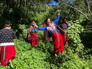 woman poses with an excited smile and arms in the air in the jungle in Chajul as if in celebration