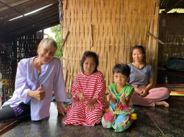 dalyn sits with a mom and two young girls in Thailand giving donated clothing