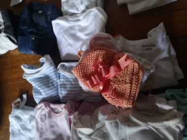 a stack of baby clothes tied together with a ribbon, sitting on top of a pile of more baby clothes