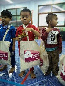 three boys pose with donated clothing bags in buengkan thailand village school classroom
