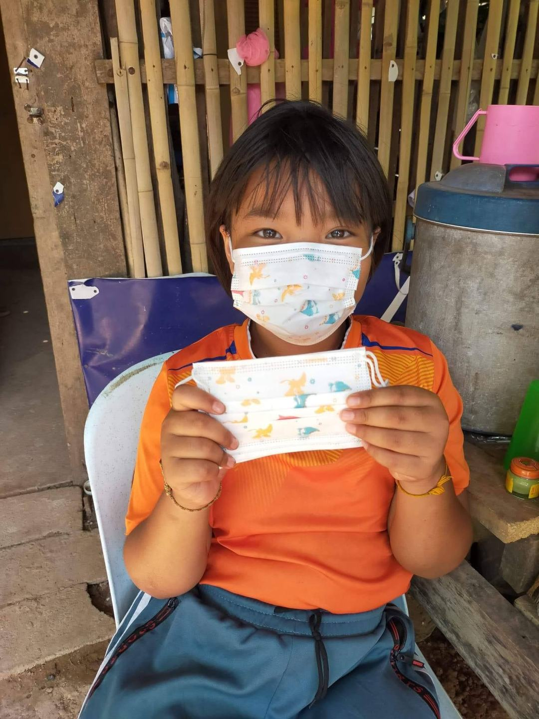 girl wearing a medical mask and holding another one
