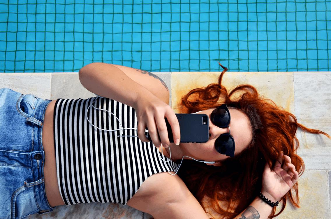 mulher deitada na piscina mexendo no celular trocando o status das redes sociais