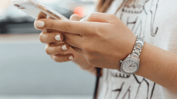 mulher mexendo no celular com relógio