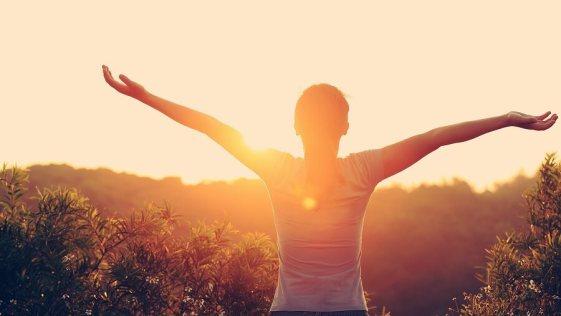mulher sozinha contemplando o por do sol