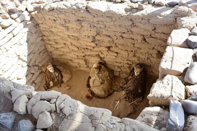 Três múmias dispostas em uma tumba do cemitério de Chauchilla