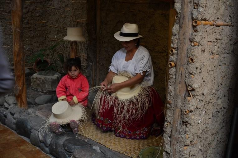 """Uma """"chola"""" cuencana e sua filha fazendo um chapéu panamá"""