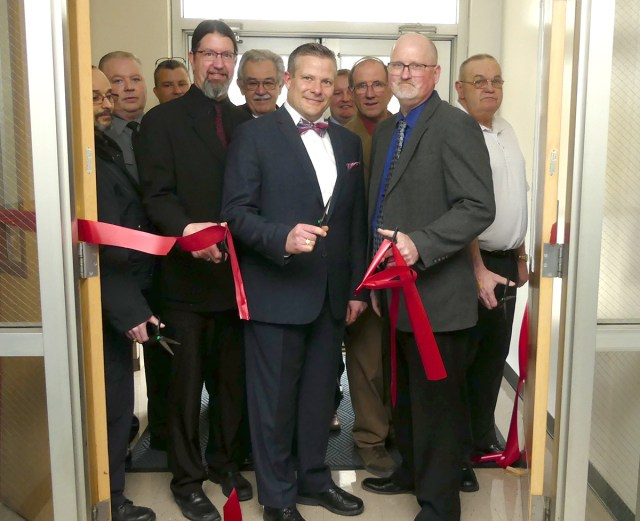 MU President Scott Barton and Scott Henry, director of MU Police Services and the Municipal Police Academy, (front) surrounded by officials from MU, area law enforcement and the Tioga Co. Commissioners, cut the ribbon to officially dedicate the Mansfield University Municipal Police Academy and Regional Training Center.