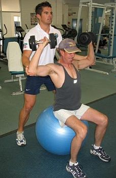 personal-trainer-spotting-shoulder-dumbbell-press-exercise-ball.jpg