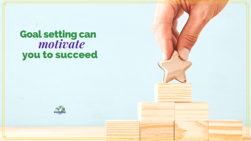 "hand placing wooden star on top of wooden block pyramid and text overlay ""goal setting can motivate you to succeed"""