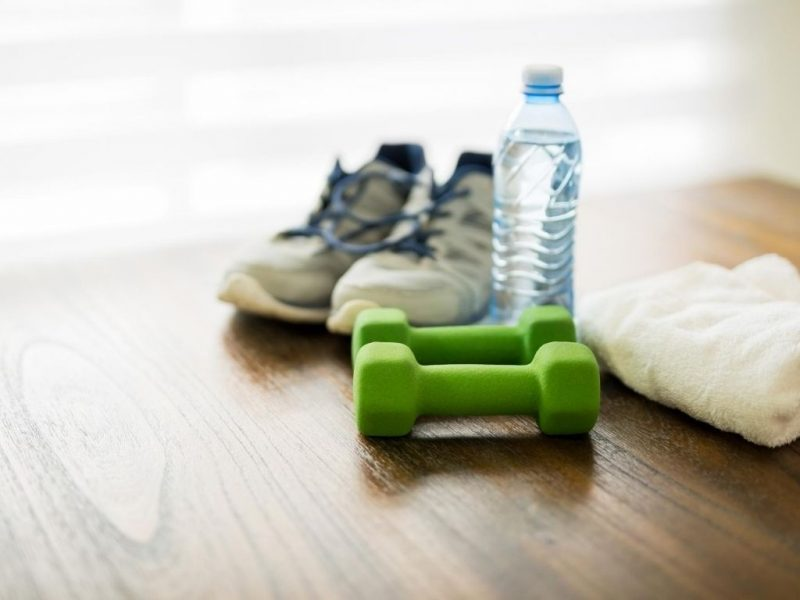 athletic shoes, water bottle a towel and small hand weights