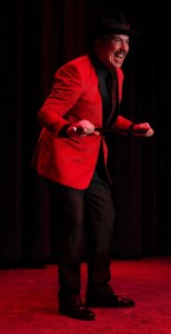 Terry Lewis, dressed in red jacket and black pants, performs as Applegate in 'Damn Yankees.'