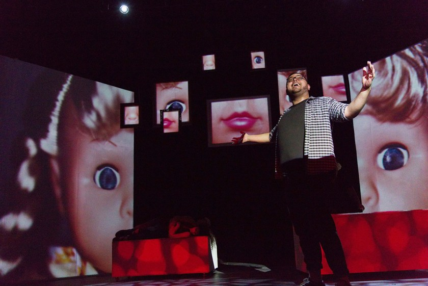 Man singing on stage in 35MM: A Musical Exhibition with images of doll face behind him.