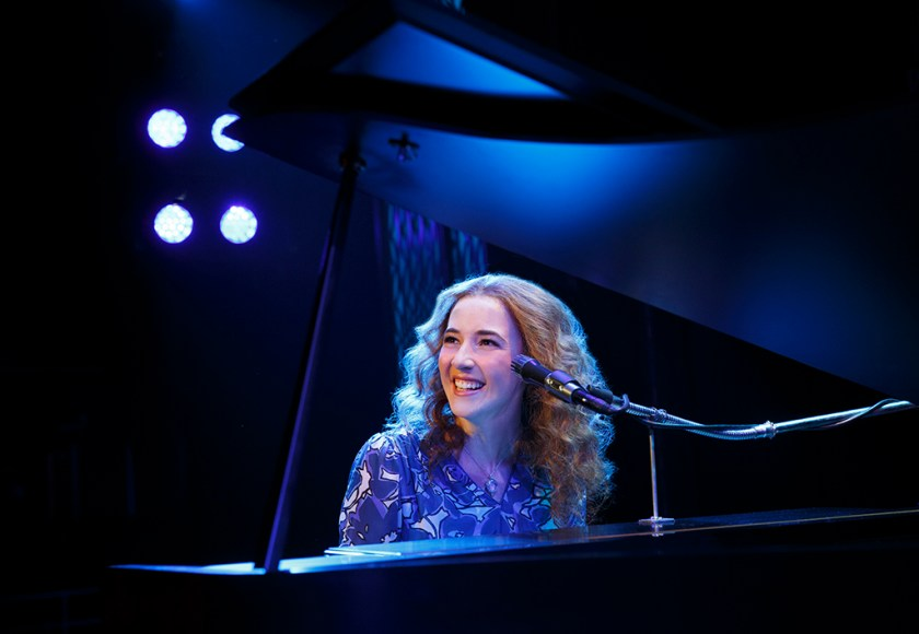 Actress playing Carole King sitting at piano.