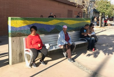 Pedestrians sit on a bench under one of Joyce Aiken's 1964 mosaics.