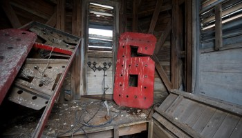 A large red number six is propped in the corner of a pigeon pooed bell house