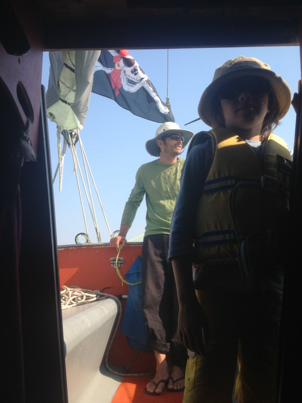 The Jolly Roger flies in the smoky breeze. A christmas present from Anand, a surviving artefact, as is it with us on the yacht, the flag to fly when children are aboard. David and Sage gaze at what remains.