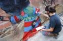 Skount pintando en La Escocesa el mural 'Trash in head'