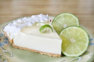 Slice of key lime pie with fresh limes and a garnish.