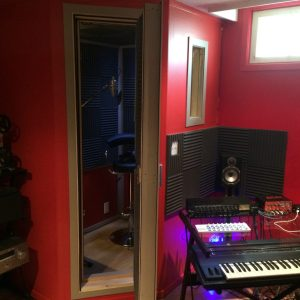 Exterior view of vocal isocaltion recording booth in corner of studio.