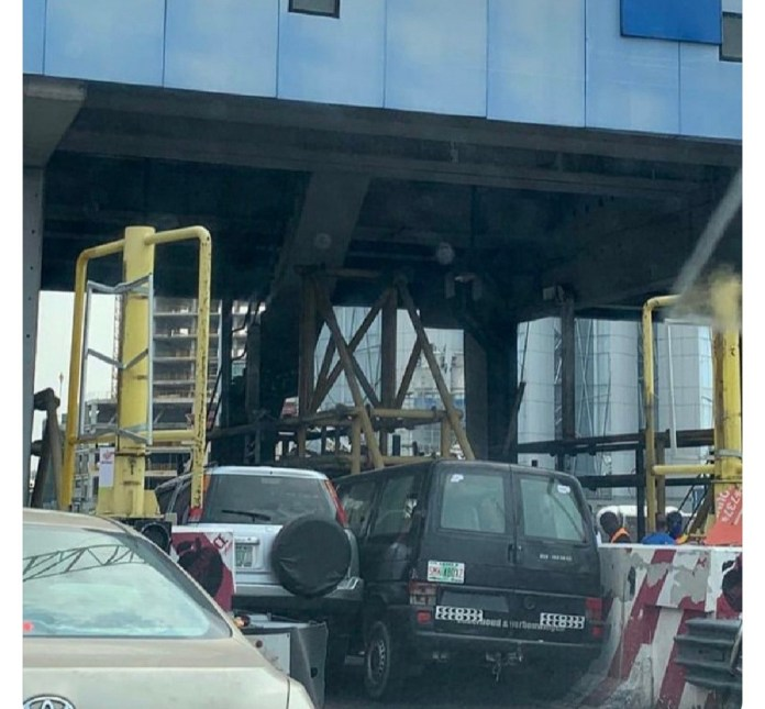 Two cars struggle to pass through Lekki tollgate at the same time