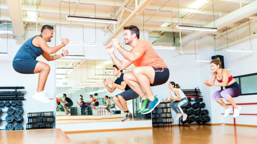 Featured | Full length of male trainer doing tuck jumps with clients in health club | How To Do Tuck Jump Exercises The Right Way