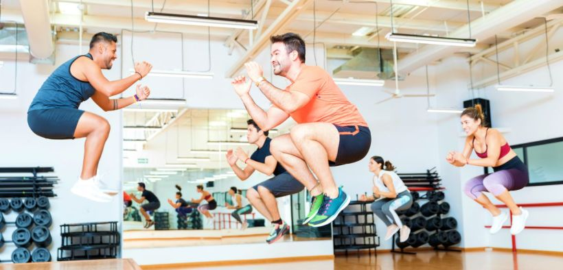 Featured   Full length of male trainer doing tuck jumps with clients in health club   How To Do Tuck Jump Exercises The Right Way