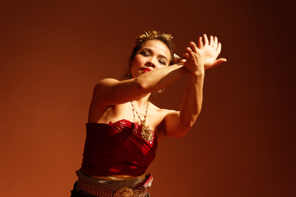 Thai traditional dancer on a red stage with eyes closed.