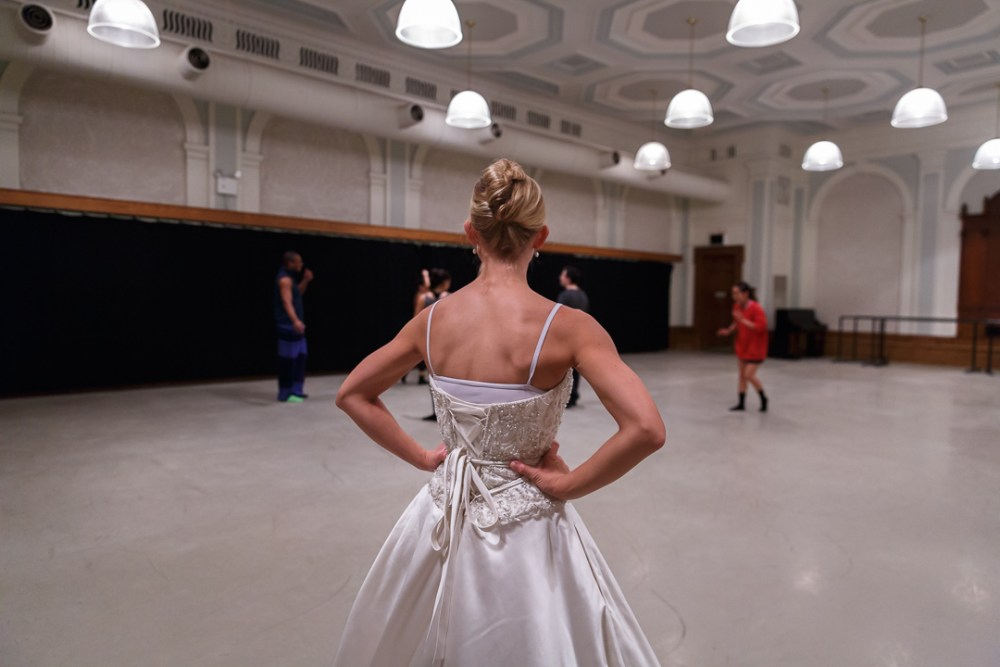 female dancer in a wedding gown looks on at rehearsing dancers