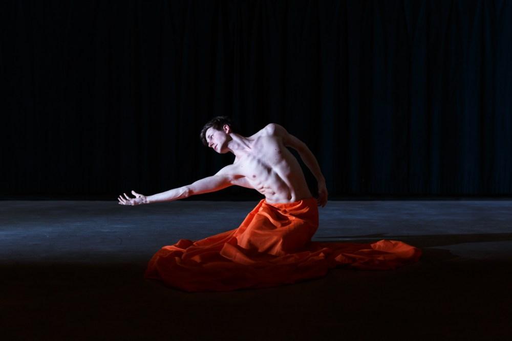 male dancer in an orange skirt kneeling
