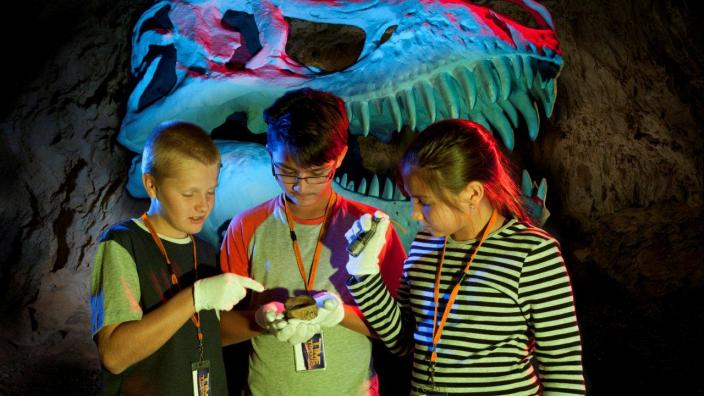 3 kids investigating a fossil