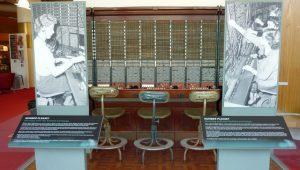 Afbeelding van een sectie van een telefooncentrale, bestaande uit rijen pluggaten. De secties is ongeveer anderhalve meter breed. Aan weerszijde zijn afbeeldingen van telefonistes te zien die eens in de centrale werkten. Voor de sectie staan drie stoelen.