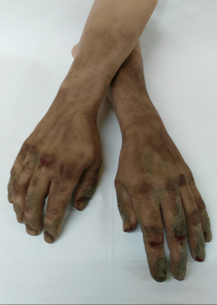 Silicone display hands with sand and blood on fingers