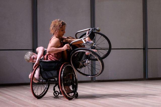 Alice Sheppard unstraps Laurel Lawson from her wheelchair as Laurel spins the partnering moment by pushing Alice's left wheel rim with both hands. Photo by Filip Wolak courtesy of Whitney Museum of American Art.
