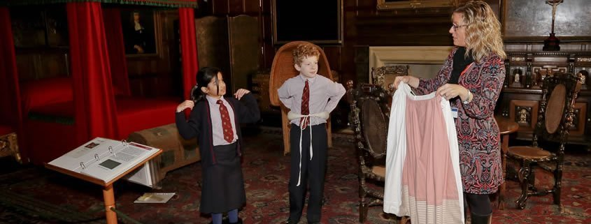 Two children in school uniform are dressing up in period costumes.