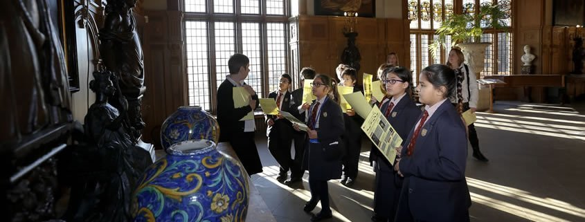 A school class is standing in the hall at Temple Newsam, listening to a visitor assistant.