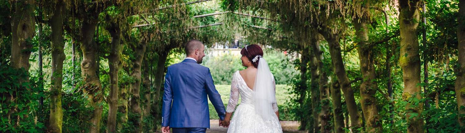 a bride and groom walk through an archway of trees.