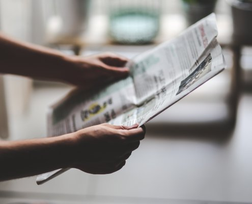 A pair of hands holding a newspaper.