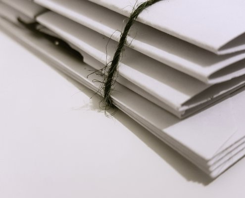 A stack of documents, bound with string.