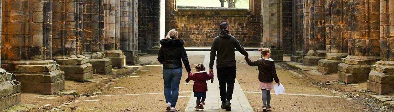 Family of four holding hands walking inside Kirkstall Abbey