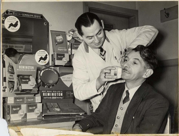 black and white photo of gentleman having a shave at a barber shop