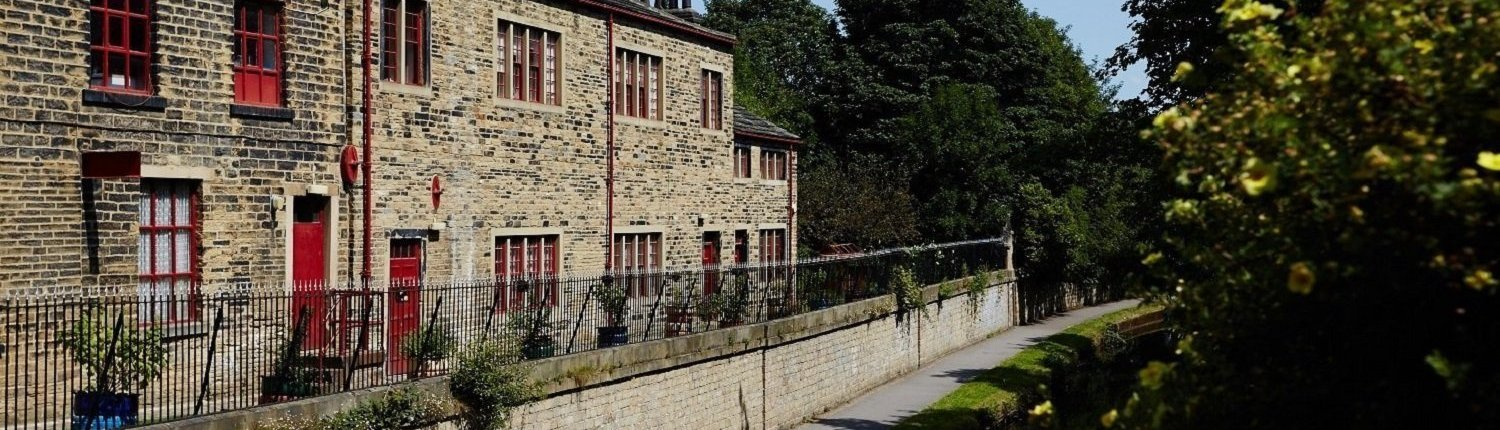 Side view of Leeds Industrial Museum with building, rails, wall and path next to a canal