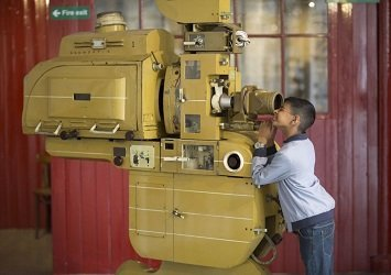 Child looking in to a large printing machine